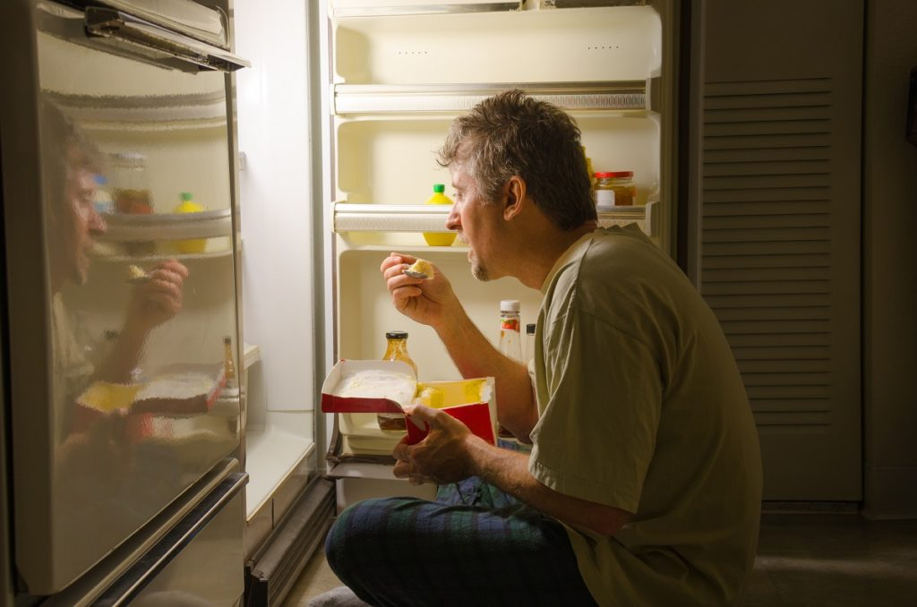 Man eating by his fridge