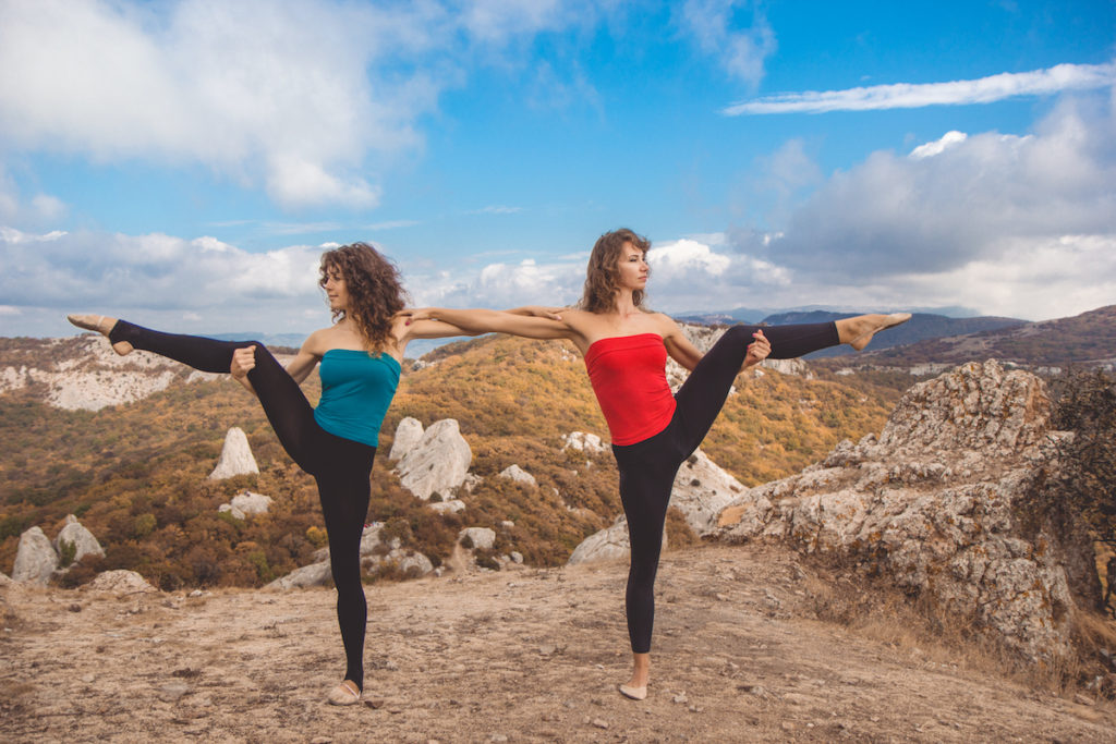 two women doing yoga in the mountains